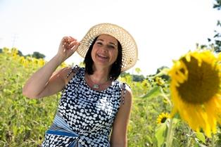 Frau in sommerlicher Kleidung auf Feld mit Sonnenblumen