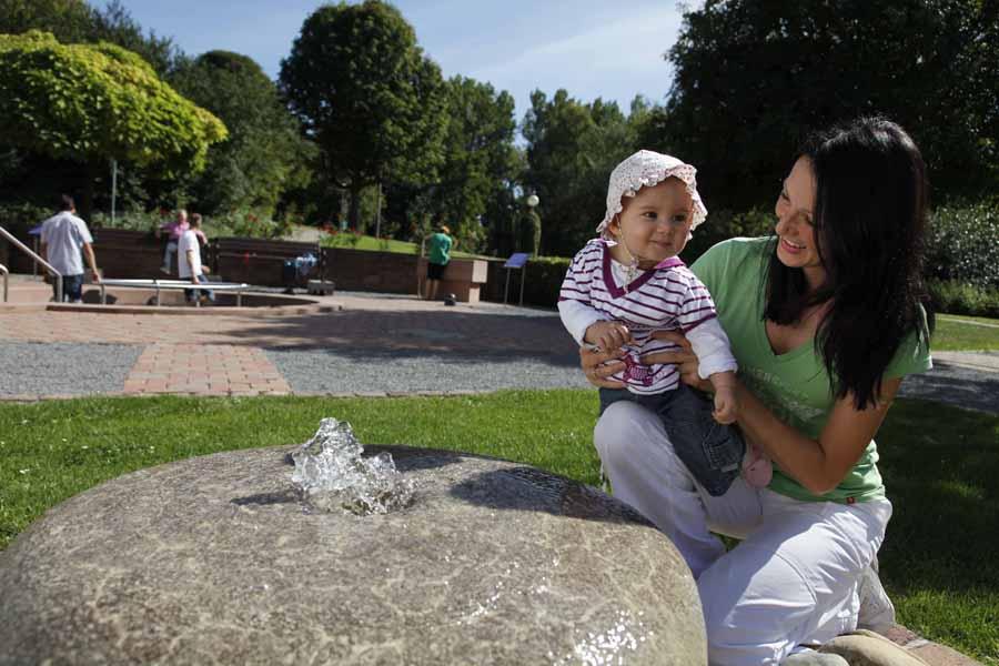 Frau mit Kind im Sommer an einem Mühlenstein mit Springbrunnen