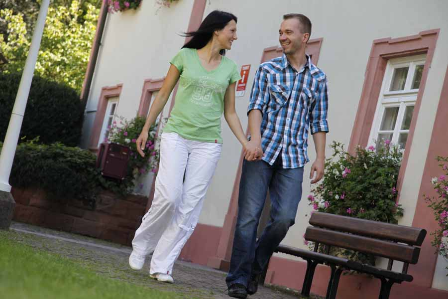 Eine Frau und ein Mann spazieren Hand in Hand im Sommer vor dem Haus des Gastes
