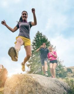 Freizeitsportler springen über ein Hindernis