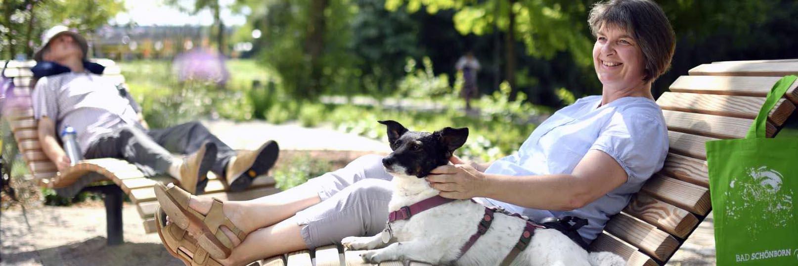 Frau und Mann mit Hund auf einer Liege im Sole-Aktiv Park Bad Schönborn