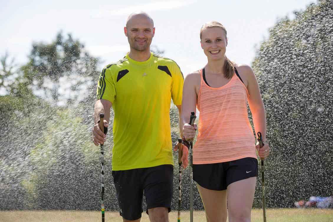 Mann und Frau mit Walkingstöcken im sommerlichen Kurpark vor einer Sprinkleranlage