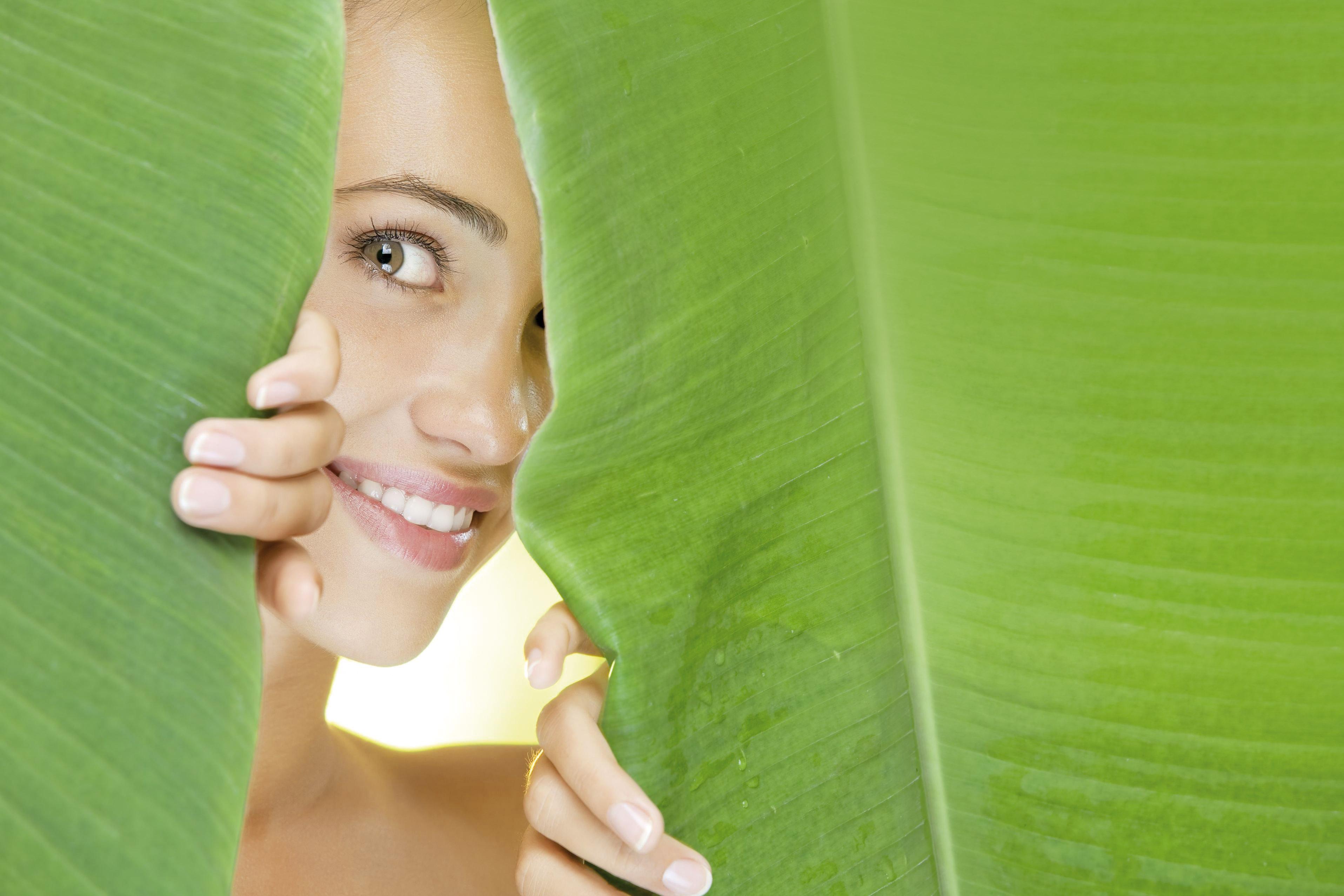 Lachende Frau hinter grünen Blättern