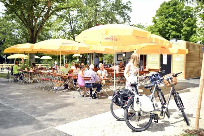 Gut gelaunte Gäste und eine Radfahrerin im Biergarten des Sole-Aktiv Park Bad Schönborn