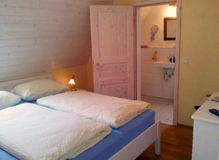 Zimmer mit Doppelbett in der Pension Kleinod Bad Schönborn