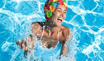 Eine gut gelaunte Frau mit bunter Bademütze im Wasser