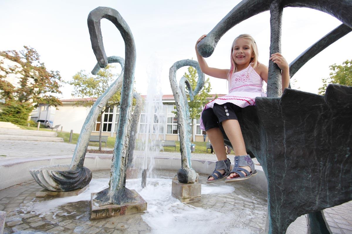 Mädchen am Springbrunnen auf dem Niederbronn-les-Bains-Platz Langenbrücken