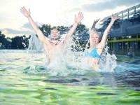 Ein Mann und eine Frau springen aus dem Wasser im Außenbecken des Thermarium Bad Schönborn