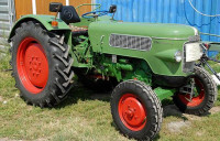 Ein grüner Oldtimer-Traktor mit roten Felgen vor einer Scheune