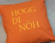 """Orangefarbenes Kissen mit aufgesticktem Text """"Hogg di noh"""""""