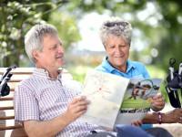 Ein Mann und eine Frau mit Walking-Stöcken lesen auf eine Bank im Sole-Aktiv Park Bad Schönborn