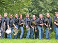 Die Musiker des Ensembles Smart Tones gut gelaunt mit Instrumenten im Freien auf einer Wiese unter Bäumen