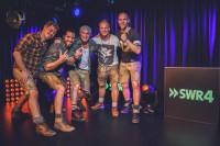 Die fünf Musiker der Band Voxxclub neben Logo SWR4
