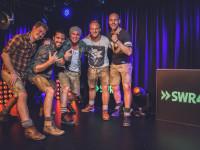 Die fünf Musiker von VoXXclub in Lederhosen neben SWR4 Logo
