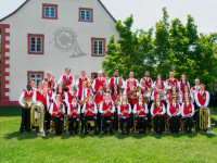 Die Musikerinnen und Musiker des Musikverein Eintracht Mingolsheim mit Instrumenten und roten Westen im Kurpark vor dem Haus des Gastes