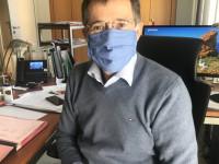 BM Huge mit Bürgermaske am Schreibtisch
