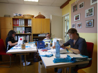 Drei Erzieherinnen sitzen an Nähmaschinen und nähen Alltagsmasken für Kollegen