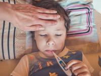 Kind mit Fieberthermometer