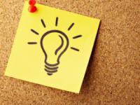 Zettel auf dem eine Glühlampe abgebildet ist auf einer Pinnwand aus Kork