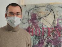 Herrn Huge links mit Maske, im Hintergrund ein Kunstwerk. Man erkennt das Wort Hoffnung