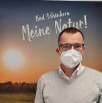Bürgermeister Huge mit medizinischer Maske im Hintergrund ein Bild von einem Sonnenaufgang mit der Aufschrift: Bad Schönborn Meine Natur!