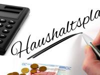 Taschenrechner und Geld, eine Hand schreibt auf einen Zettel: Haushaltsplan