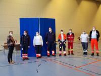 Gruppenfoto der Rettungskräfte und Mitarbeiter des mobilen Impfteams in einer großen Halle vor einem großen blauen Aufsteller. Mitarbeiterin vom Rathaus überreicht einem Mitarbeiter eine Packung Merci-Schokolade