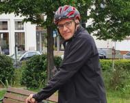 Bürgermeister Huge auf dem Fahrrad im Stand, will gerade losfahren. Im Hintergrund eine Bank
