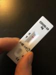 Zwei Finger halten negativen Corona-Schnelltest