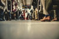 Ansicht auf einen vollen Bus von unten: Man sieht überwiegend Füße und Beine in einem vollem Bus. Die Oberkörper sind nicht zu sehen