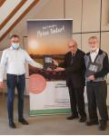 Bürgermeister Klaus Detlev Huge (links) überreicht den beiden Autoren Karl Günther (Mitte) und Hans-Georg Schmitz (rechts) die druckfrischen Exemplare ihrer Dokumentation über den jüdischen Friedhof.