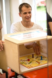 Ein Mann spielt im Rahmen des Demenzparcours ein Brettspiel ohne die Figuren sehen zu können