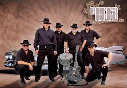 Die fünf Musiker der Happy Hours Band in schwarzen Anzügen vor einem Oldtimer