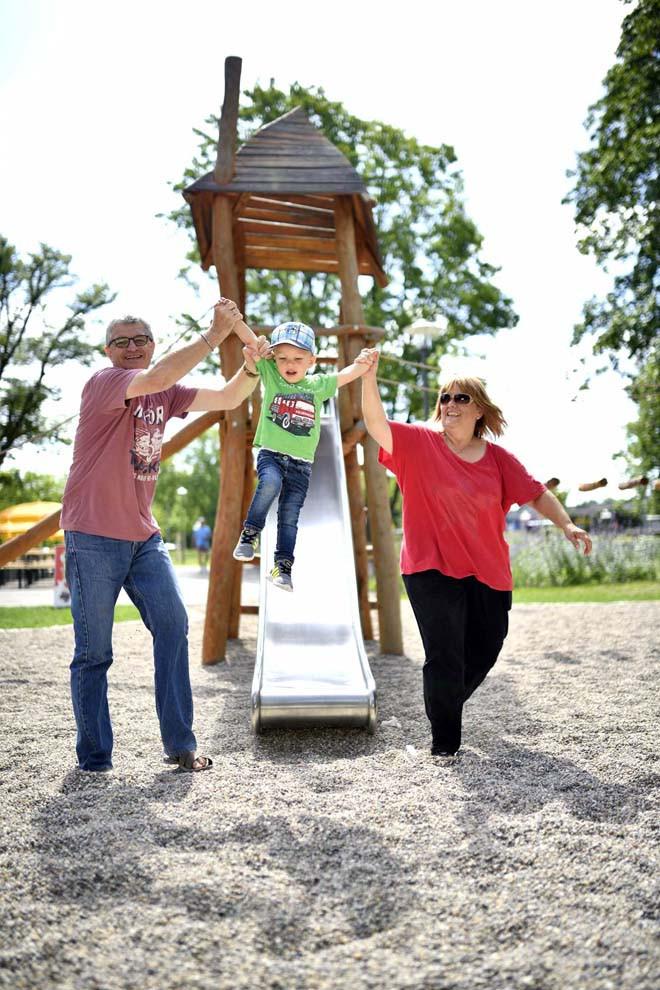 Ein Mann und eine Frau mit rutschendem Kind auf Mehr-Generationen-Spielplatz im Sole-Aktiv Park Bad Schönborn