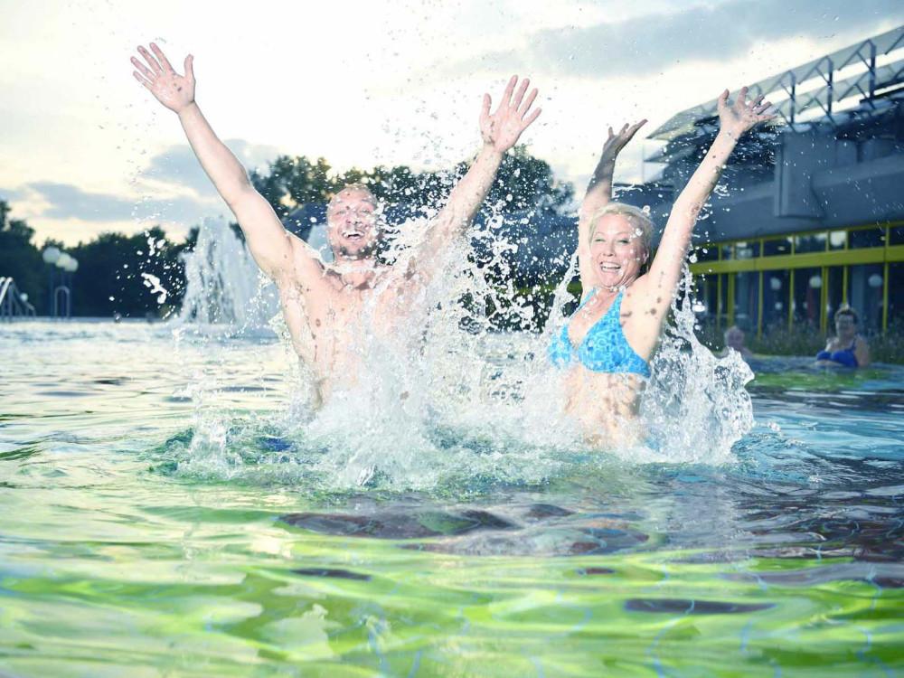 Ein Mann und eine Frau springen aus dem Wasser im Außenbecken