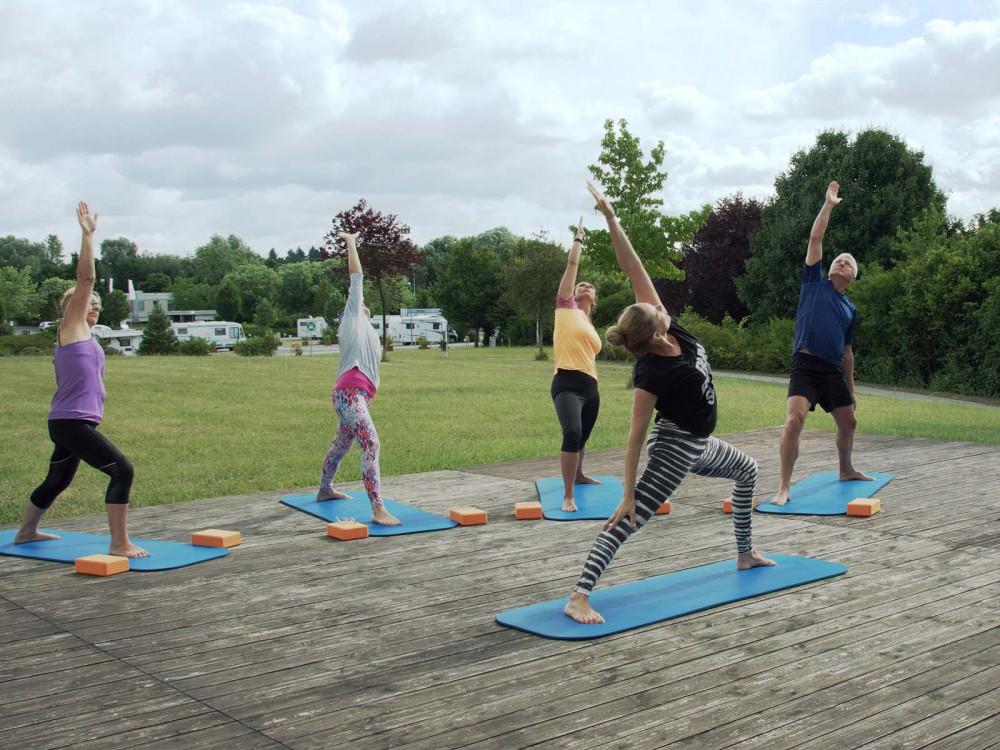 Sportlergruppe bei Rückengymnastik im Freien