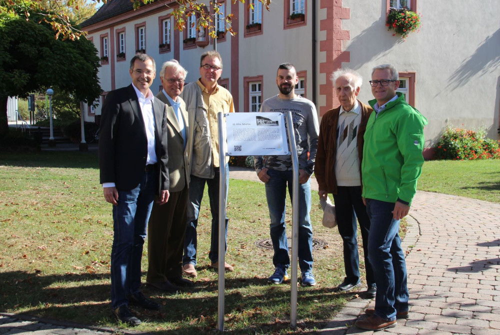 Neue Schilder, wie hier vor dem Haus des Gastes, weisen nun auf die Ortshistorie von Mingolsheim hin. Am Projekt beteiligt waren unter anderem: v.l.n.r.: Bürgermeister Klaus Detlev Huge, Herbert Göbel, Gerhard Kohl, Patrick Wirth, Rudolf Schmich und Touri