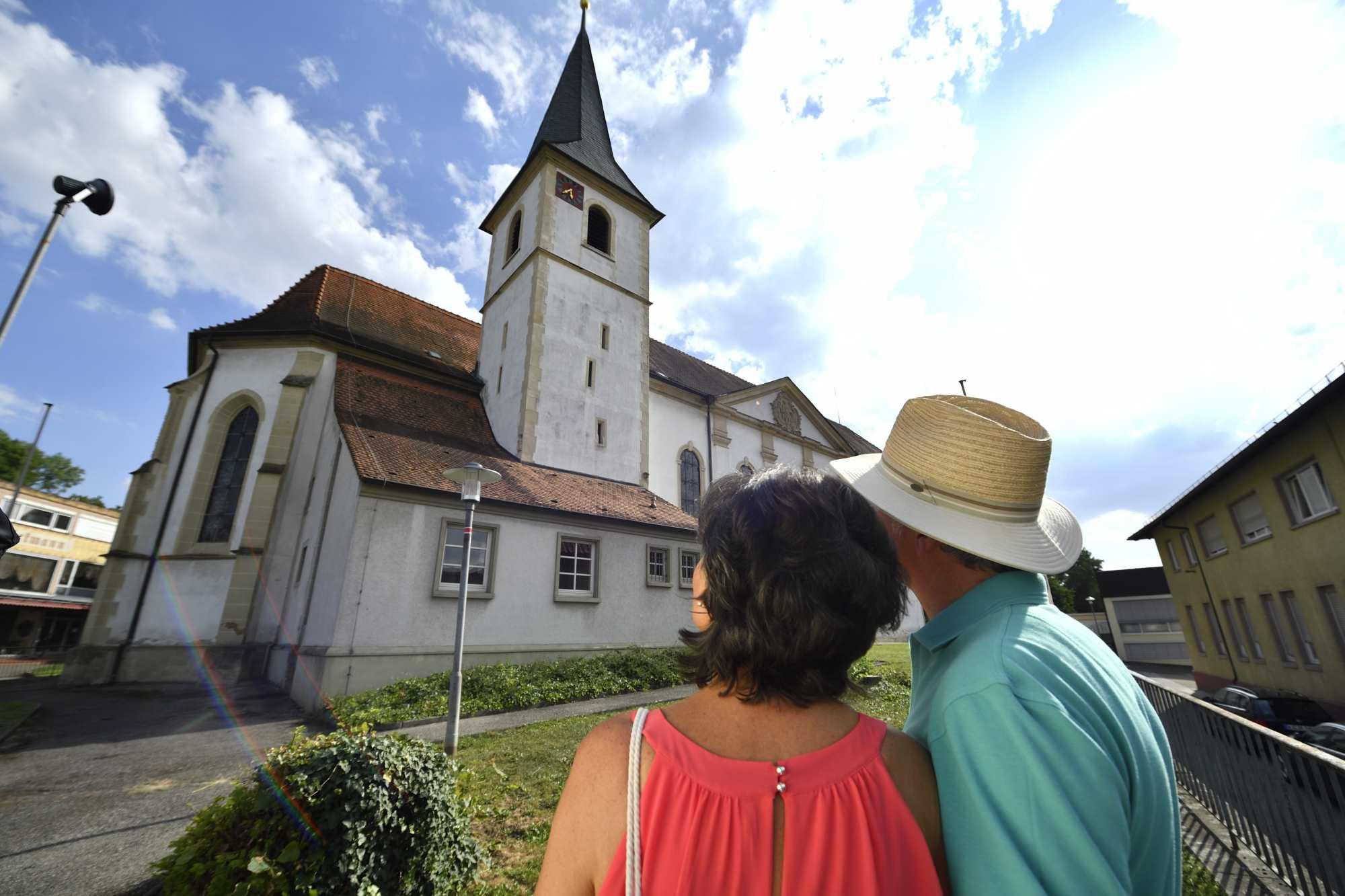 Eine Frau und ein Mann schauen auf die Pfarrkirche Langenbrücken