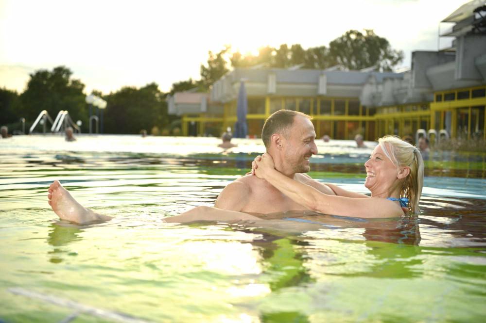 Eine Frau und ein Mann entspannen gut gelaunt im Außenbecken des Thermarium Bad Schönborn