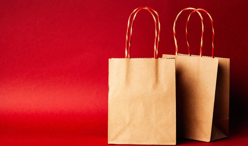 Zwei Papiertüten vor rotem Hintergrund