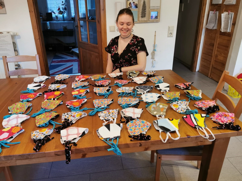 Eine 17-jährige Frau sitzt am Tisch mit 70 selbstgenähten Alltagsmasken.