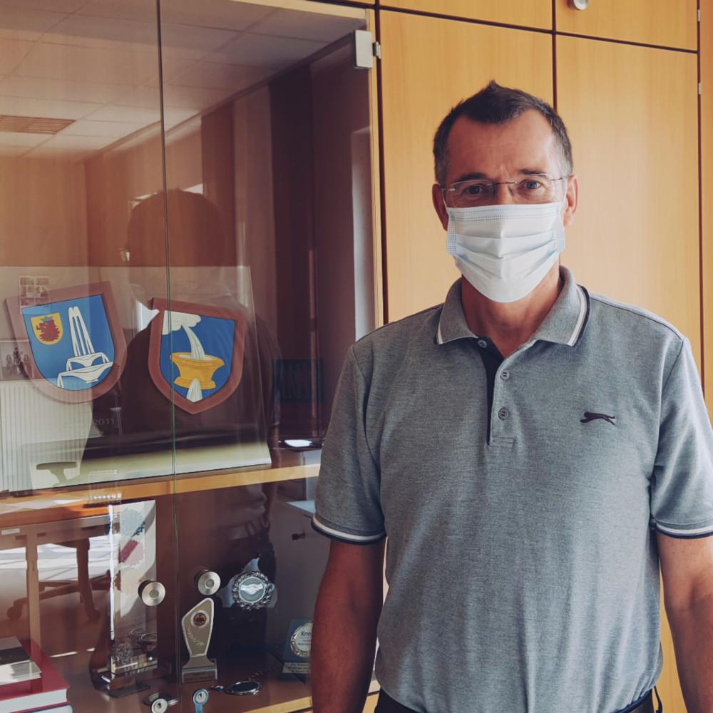 Foto von Bürgermeister Huge (Mann mittleren Alters) mit Maske. Im Hintergrund ist ein Schaufenster mit Wappen und Münzen