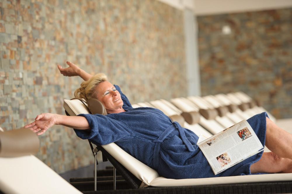 Frau im blauen Bademantel mit Zeitschrift auf einer Liege im Ruheraum im Thermarium Bad Schönborn