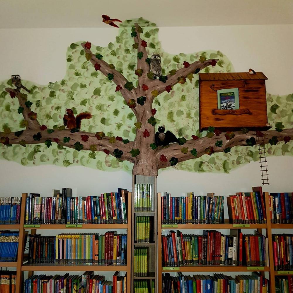 Regale mit Bücher, im Hintergrund ein gebastelter Baum mit Vogelhäuschen