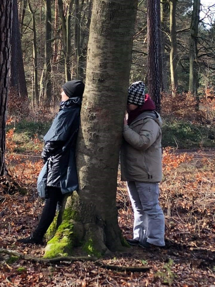 Zwei Frauen lehnen an einem Baum