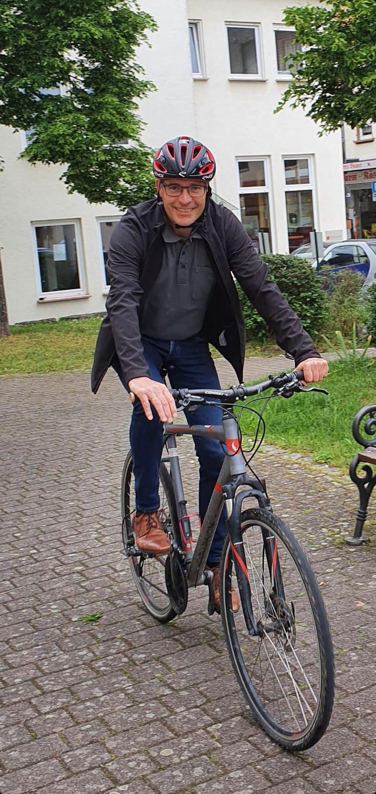 Bürgermeister Huge fährt auf dem Fahrrad mit Fahrradhelm