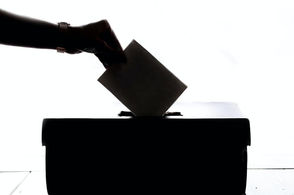 Silhouette Wahlurne und Hand mit Wahlschein